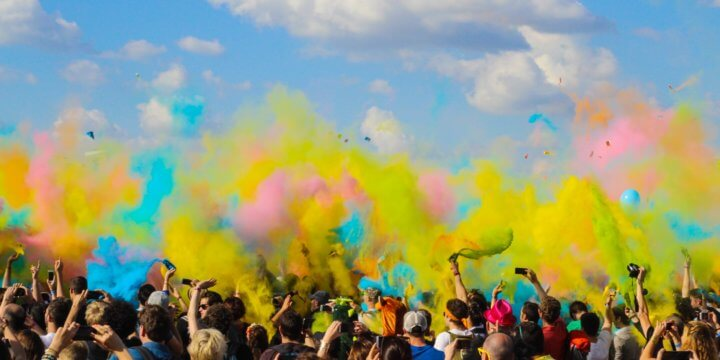group of people throwing dry paint into the air in a color race on a sunny day