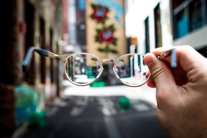 Glasses in the foreground with tall buildings in the background