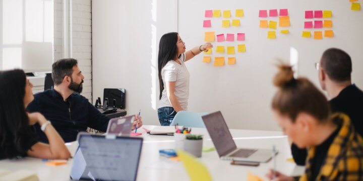 A group of people gathered around a white table and wall of colorful post-its