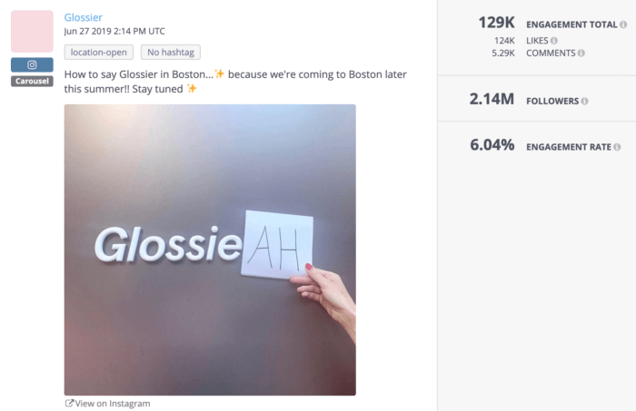 """Glossier's logo on a grey background with the """"r"""" swapped for """"ah"""""""